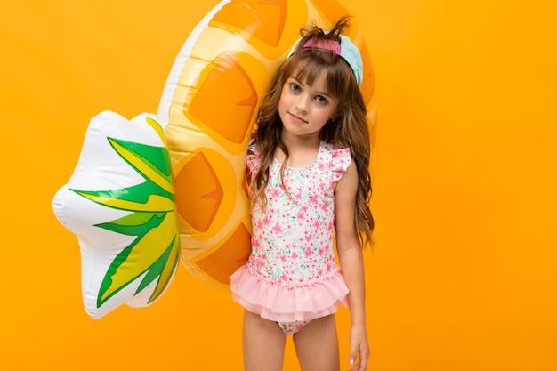 Kind mit einer baseballkappe in einem badeanzug mit einem schwimmkreis, ananas auf einer orange wand