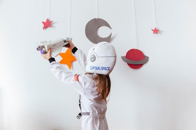 Kind mit einer handgemachten galaxie zu hause