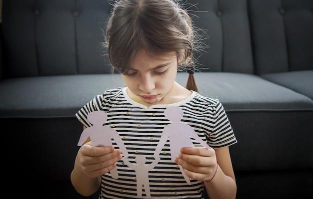 Kind mit einer papierfamilie in seinen händen.