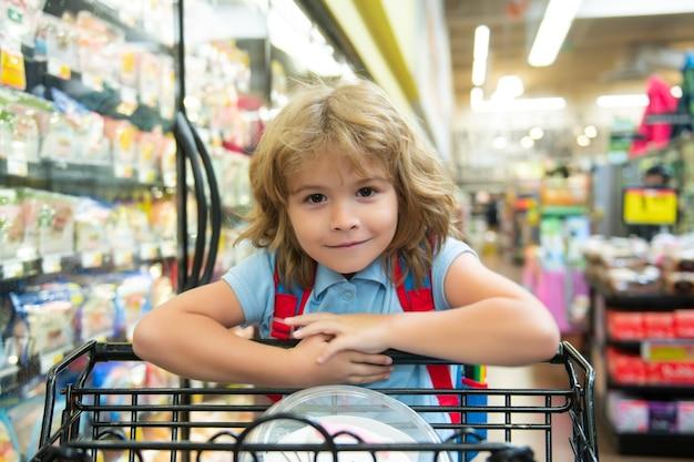 Kind mit einkaufskorb, der lebensmittel in einem lebensmittelgeschäft kauft. kundenkind, das produkte im supermarkt kauft