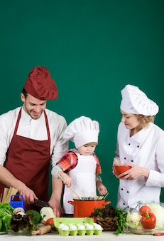 Kind mit eltern, die am küchentisch kochen, entzückendes kind in kochmütze, glückliche liebevolle familie, die sich vorbereitet