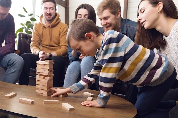 Kind mit eltern, die brettspiele spielen, lustige zeit zu hause mit familie und freunden. hochwertiges foto
