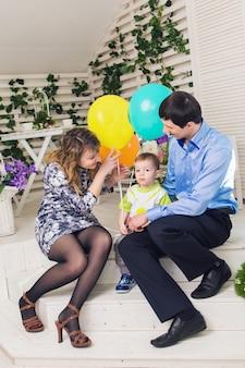 Kind mit eltern, die geburtstag feiern. glückliche familie, die zusammen geburtstag feiert.