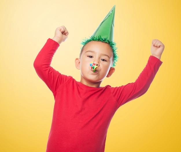 Kind mit erhobenen armen und partygebläse