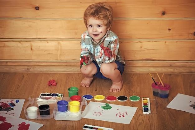 Kind mit farbigen händen, gouachefarben und zeichnungen. kind spielt. konzept für fantasie, kreativität und freiheit. kunsthandwerk für kinder. malermalerei auf holzboden.