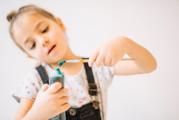 Kind mit farbtube und pinsel in den händen