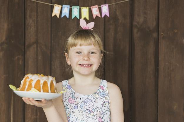 Kind mit feiertagskuchen auf platte