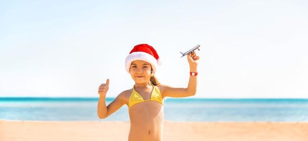 Kind mit flugzeugen in der hand am strand