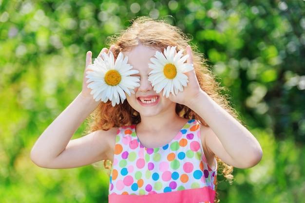 Kind mit gänseblümchenaugen, auf grünem bokeh hintergrund