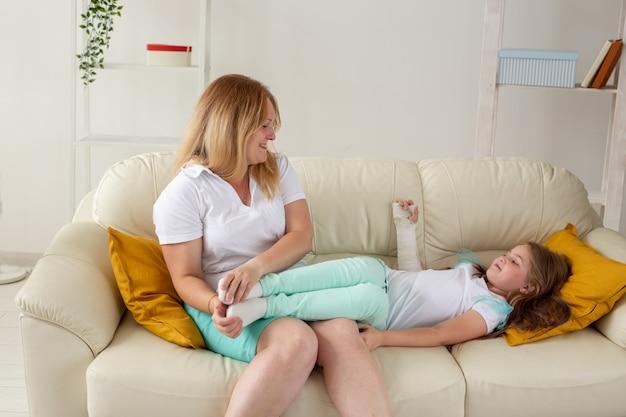Kind mit gebrochenem arm und gips verbringen zeit zu hause mit der mutter