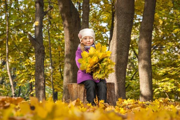 Kind mit gelben blättern, einem strauß gelber blätter, gefallenen blättern, ahorngelben blättern, gelben blättern von vinok