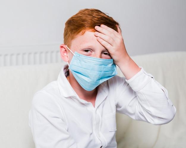 Kind mit gesichtsmaske und kopfschmerzen