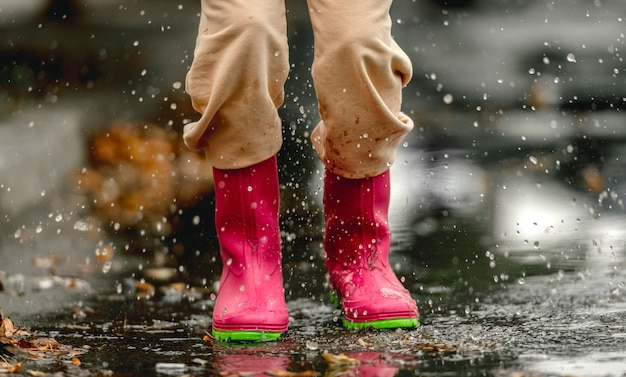 Kind mit gummistiefeln, die an regnerischen tagen im herbst in einer pfütze stehen. kinderfüße in gummistiefeln im freien in der herbstsaison