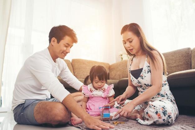 Kind mit ihrem elternteil, das auf fußboden im wohnzimmer spielt