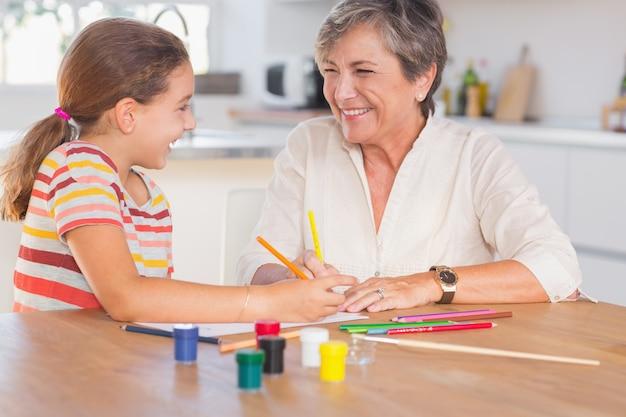 Kind mit ihrer oma zeichnen und lachen