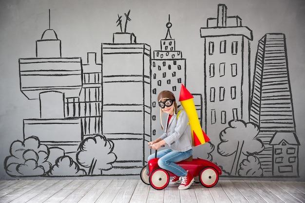 Kind mit jetpack. kind, das zu hause spielt. erfolgs-, vorstellungs- und innovationstechnologiekonzept