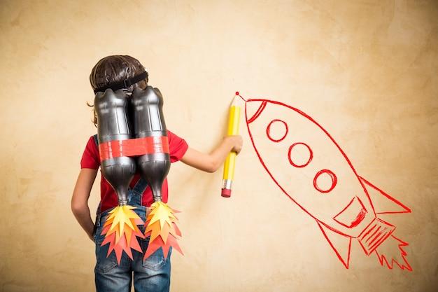 Kind mit jetpack zeichnen skizze an der wand. kind, das zu hause spielt. erfolgs-, leader- und gewinnerkonzept