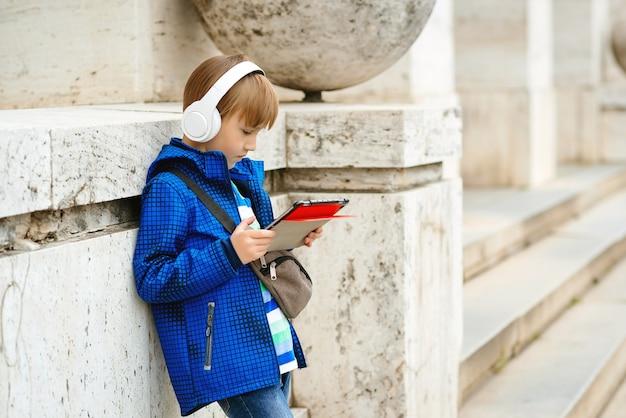 Kind mit kabellosem kopfhörer. stilvoller junge, der die straße geht und musik genießt. menschen, technologie und lebensstil.