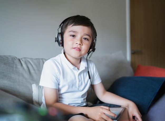 Kind mit kopfhörer, das musik mit einem digitalen tablet hört