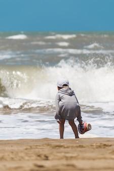 Kind mit korb am ufer des meeres in der nähe von wasser