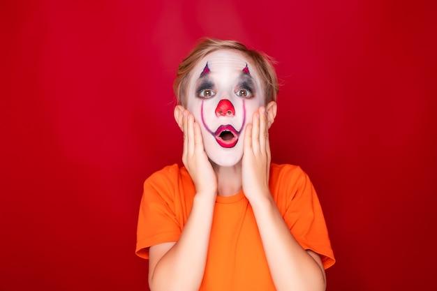Kind mit make-up, dann packte halloween mit beiden händen vor erstaunen und angst sein gesicht.
