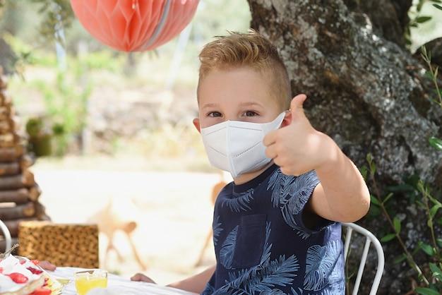 Kind mit maske im freien, das der neuen normalität zustimmt