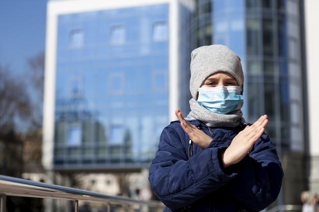 Kind mit medizinischer maske, die x zeichen außerhalb zeigt