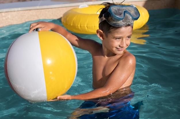 Kind mit mittlerem schuss, das ball hält