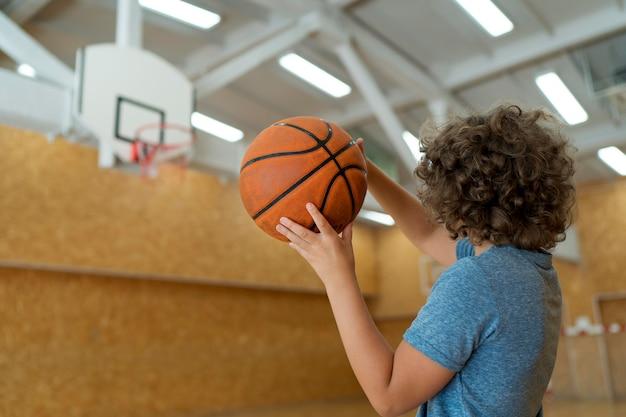 Kind mit mittlerem schuss, das basketball hält