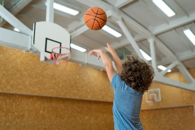 Kind mit mittlerem schuss, das basketball wirft