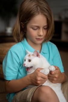 Kind mit mittlerem schuss, das eine entzückende katze hält
