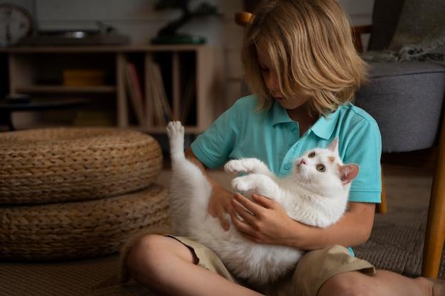 Kind mit mittlerem schuss, das katze hält