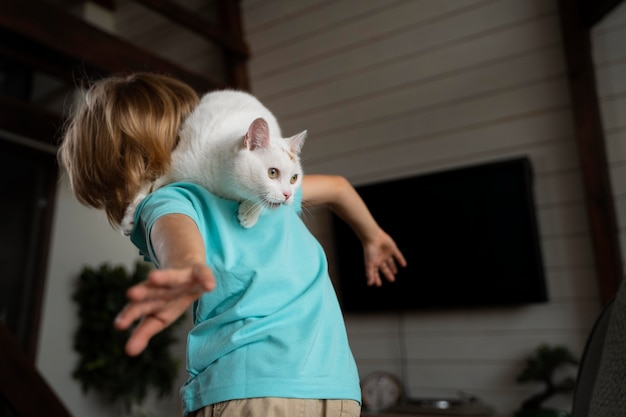 Kind mit mittlerem schuss, das mit katze spielt