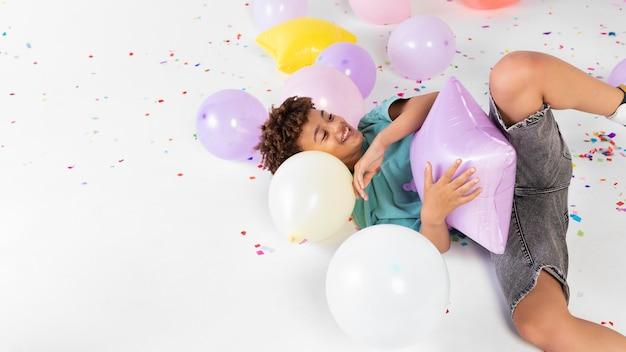Kind mit mittlerem schuss, das mit luftballons spielt