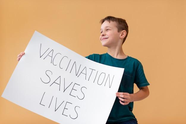 Kind mit mittlerem schuss, das plakat hält