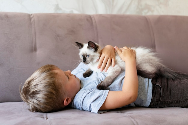 Kind mit mittlerem schuss, das süße katze hält