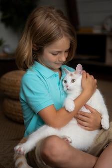 Kind mit mittlerem schuss, das weiße katze hält