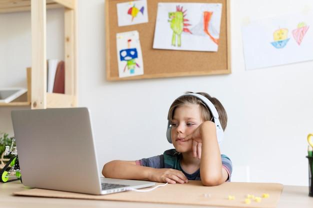 Kind mit mittlerem schuss sitzt am schreibtisch