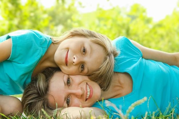Kind mit mutter spielen draußen in einem park auf der mutter im gras