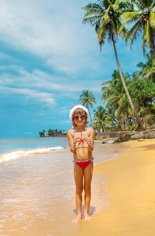 Kind mit nikolausmütze und sonnenbrille hält ein geschenk am strand