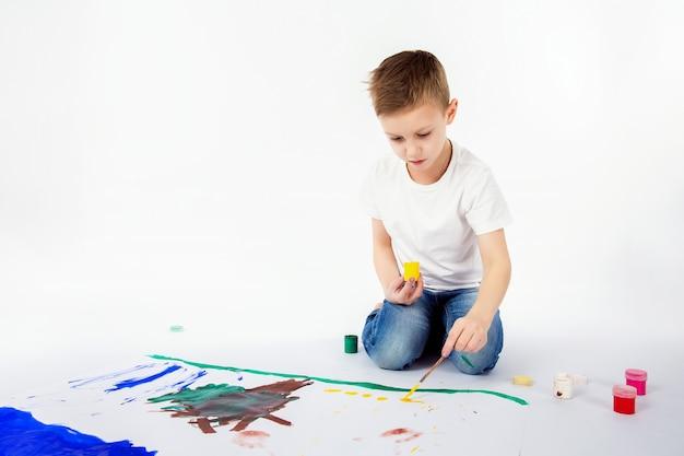 Kind mit pinsel. 9-jähriger junge, moderne frisur, weißes hemd, blue jeans zeichnet den lokalisierten pinsel.
