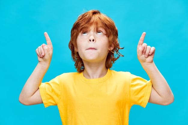 Kind mit roten haaren zeigt mit dem zeigefinger nach oben