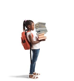 Kind mit rucksack und einem stapel bücherbücher