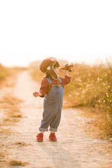 Kind mit spielzeugflugzeug in der natur bei sonnenuntergang