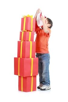 Kind mit stapelgeschenkbox. isoliert im weißen hintergrund