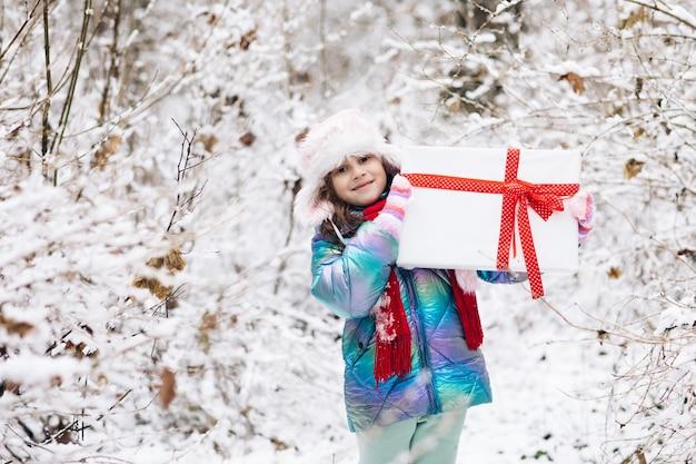 Kind mit weihnachtsgeschenken und geschenken im schnee.
