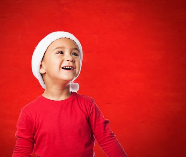 Kind mit weihnachtsmann-hut nachschlagen
