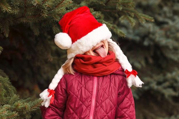 Kind mit weihnachtsmütze zog es über ihre augen und streckte die zunge heraus