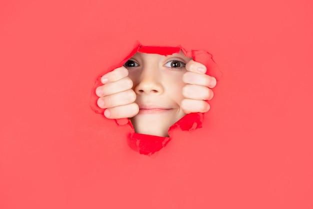 Kind mit zahnigem lächeln zeigt gesicht im papierloch. positives kind mit einem angenehmen lächeln im gesicht, hält sich durch ein zerrissenes loch in gelbem papier. papierhintergrund brechen. emotionen-konzept.
