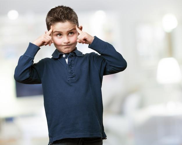 Kind mit zeigefinger auf dem kopf